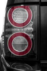 Detail on the rear light of a black car.