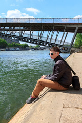 young man resting on the River Seine, Paris, France
