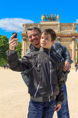 Man and teen in Paris take a selfie in front of The Arc de Triom