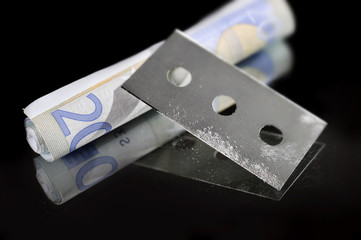 cocaine bag and drug razor blade in addiction concept