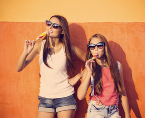 two girls with ice-cream on background wall