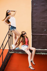 two teenager girls on background wall
