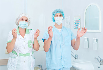 Medical staff sterilizing hands and arms before surgery