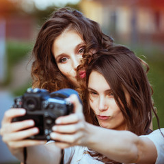 two beautiful young happy girls make self-photo