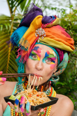 girl with bright makeup eating noodles