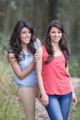 portrait of beautiful brunette sisters in a forest