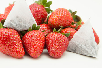 Pile of strawberry fruits and tea bags isolated
