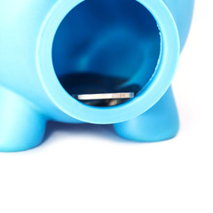 Closeup piggy bank with coins isolated on white background.