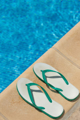 Pair of flip flop thongs and a towel on the side of a swimming