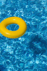 Yellow pool float, pool ring in cool blue refreshing water