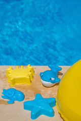 Various water toys on the side of a swimming pool