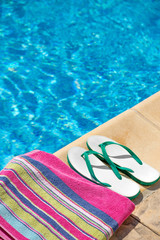 Pair of flip flop thongs and towel on the side of a swimming
