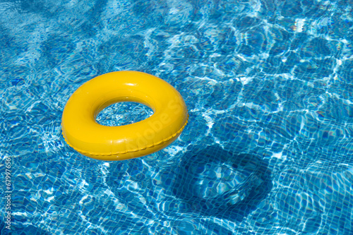 Staande foto Duiken Yellow pool float, pool ring in cool blue refreshing water
