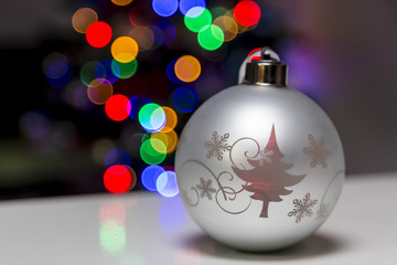 Silver Christmas lightniing ball on a reflective table