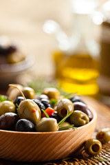 Marinated olives in wooden plate.