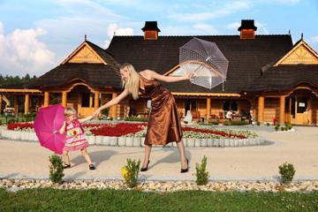 Mama z małą córeczką bawią się parasolkami.
