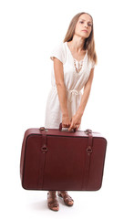 woman lifts a heavy suitcase, isolated on white