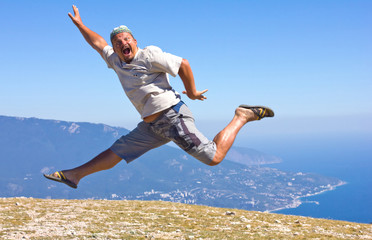 happy man jumping on a background of mountains and sky and sea