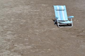 Blauer Strandstuhl im Sand