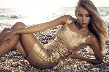 sexy girl with blond hair in gold dress posing on beach