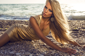 girl with blond hair in gold dress posing on beach