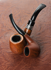 Tobacco pipes on leather background