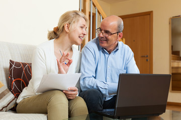 Mature couple with laptop in home