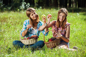Happy young girls with a fruit basket on nature