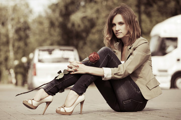 Sad young fashion woman with a rose sitting on the road