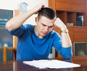 Frustrated man looking at financial document