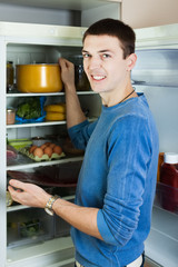 guy searching for something in refrigerator