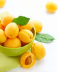 Ripe Organic Apricots with leaves on a white wooden table