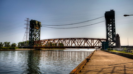 A timelapse of a boat passing under a lift bridge
