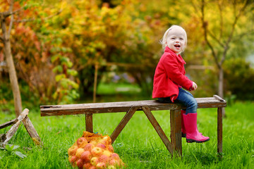 Little toddler girl sitting on a wooden bench