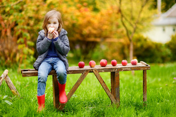 Cute little girl sitting on a wooden bench
