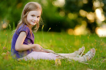 Cute little girl sitting on the grass
