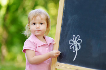 Adorable toddler drawing with a chalk