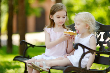 Two little sisters sharing delicious cream tart