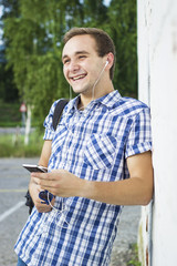 Smiling young man listening to music outdoor