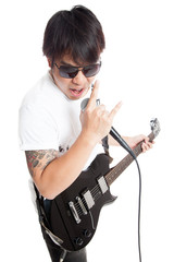 Asian rocker play guitar and sing with rock hand sign