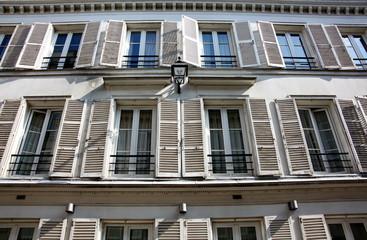 Façade d'immeuble ancienne avec volets blancs