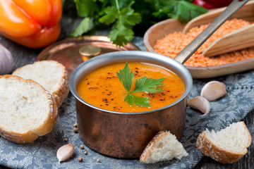 red lentil soup with pepper and spices in a copper saucepan