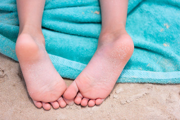Little girl feet on a beach towel