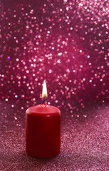 Red candle. Red glittering christmas lights.