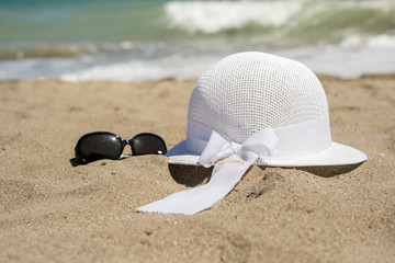 Wicker white hat and sunglasses on the beach