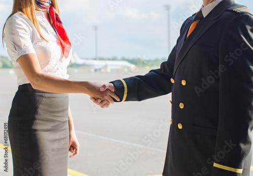 Leinwanddruck Bild Pilot and stewardess shaking hands on airfield background.