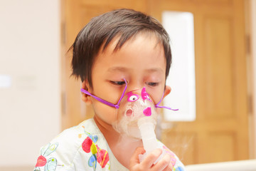 little boy lying in bed with inhalator mask