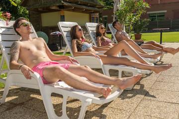 Four friends sunbathe on the sun loungers on the beach