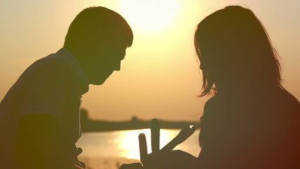 Young couple in love eating ice cream at sunset on the lake