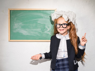 Schoolgirl at the blackboard in the classroom